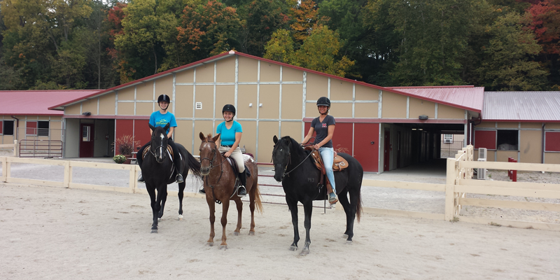 wide shot of three riders and their horses