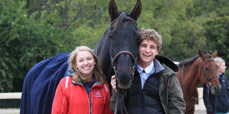 two students posing with a horse
