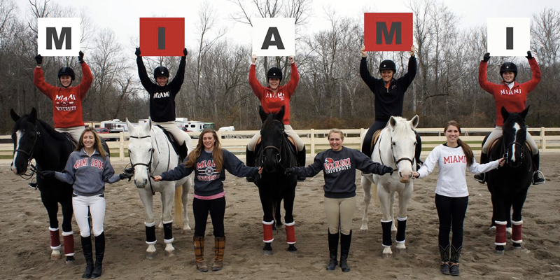 team members holding up letters on horses