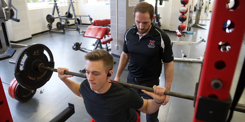 Student lifts weights with the help of a trainer in Martin Fitness Center.