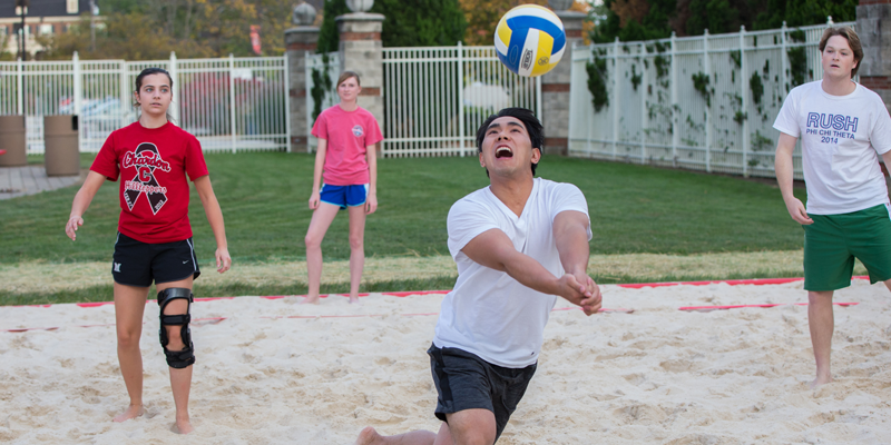 Students playing sand volleyball.