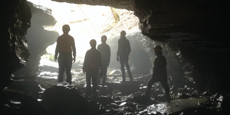 Group standing in cave, staring out towards the light in an epic manner