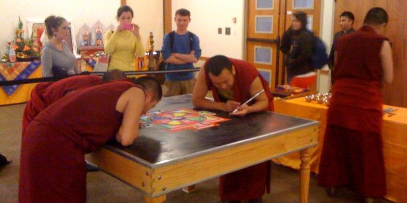 Students observing the creation of art by Buddhist monks