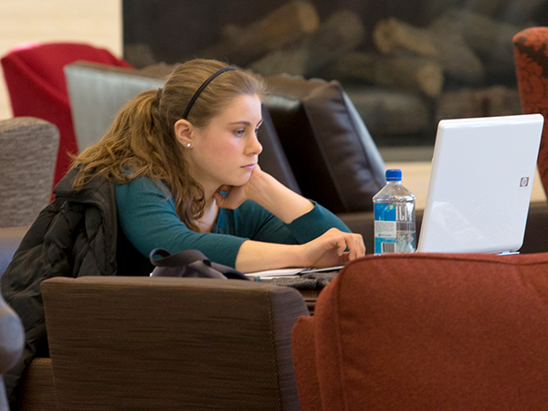 A female student working on her laptop computer at a table