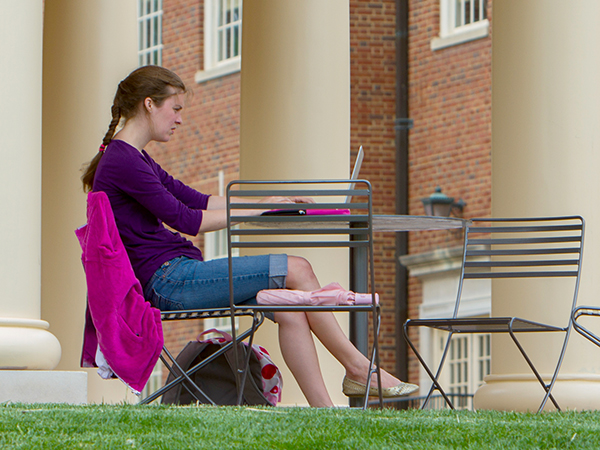 A student does her homework at a table on the Armstrong pavillion