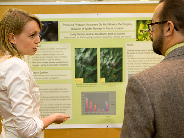 Student presenting a research poster to her professor