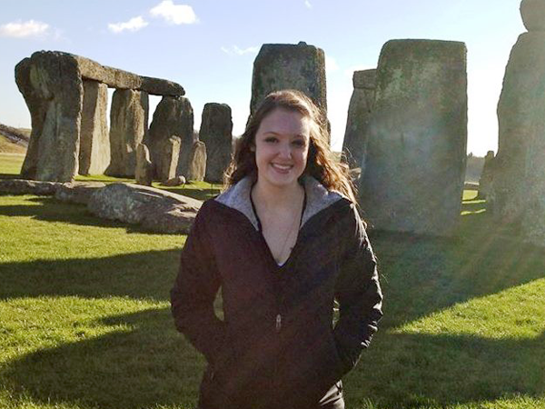 A student stands in front of a Stonehenge