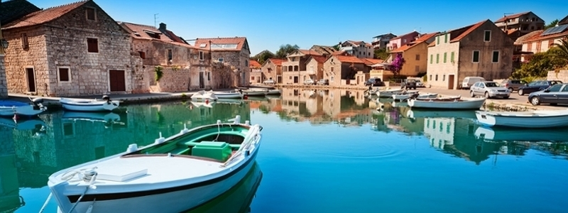 Beautiful coastline of Croatia, old buildings and a boat.