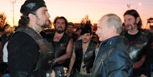 Putin stares at a biker-man much taller than him.