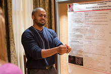 student talking in front of research poster