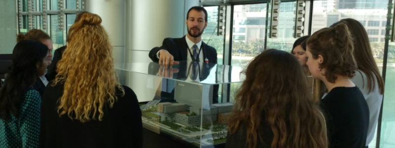 Students examine an architectural model of a modern building complex