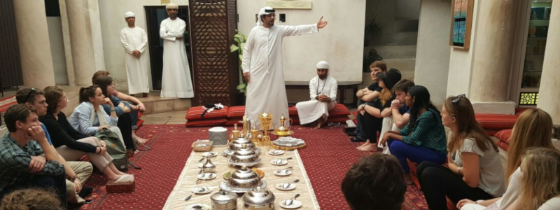 Students prepare to eat a meal seated on the floor in traditional Arab fashion
