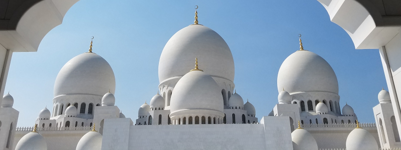An imposing white mosque with many domes of different sizes