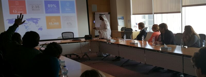 Students in a boardroom watch a PowerPoint presentation by a man in traditional Arab dress