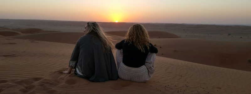 Two students sit on a dune watching a desert sunset