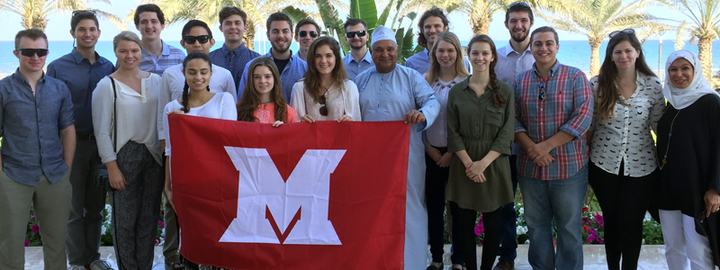 Students pose with a Miami flag, along with the family of an Omani Miami alum