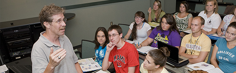 Students listen as a professor lectures in the classroom