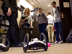 Students observe a small wheeled robot