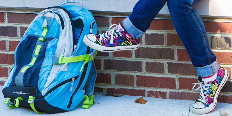 blue backpack next to girls feet with brightly colored shoes