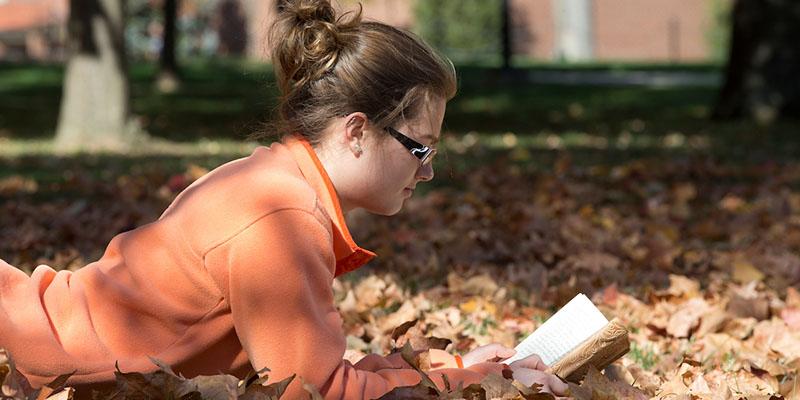 girl lying in leaves reading book