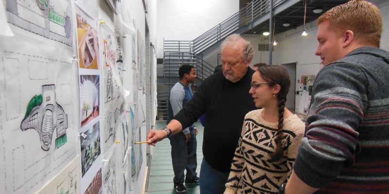 Craig Hinrichs looking at drawings with two grad students