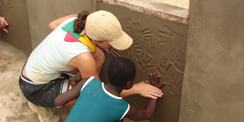 child putting handprint on wall in ghana