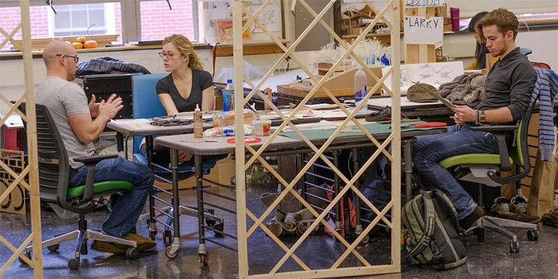 Professor and 2 students converse at a rectangular table in the studio, as seen through a lattice