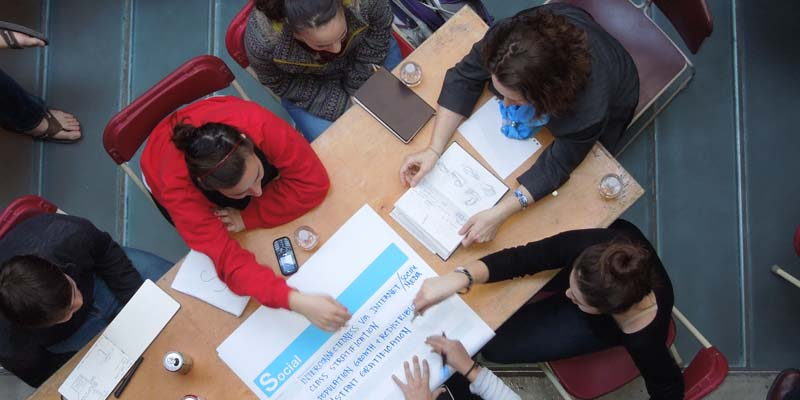 Seen from overhead, several students seated at a rectangular table collaborate on a project