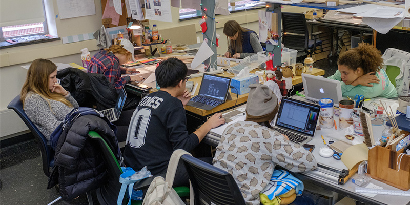 A group of students seated at rectangular studio tables work on projects using art supplies and computers. The tables are covered with assorted supplies such as drawing and cutting implements
