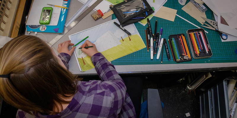 A woman is seen from overhead as she uses colored pencils to work on a drawing