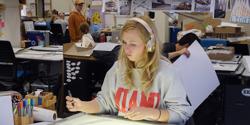 A woman wearing a Miami shirt and headphones is seated at a worktable. She holds a pen and works on a drawing