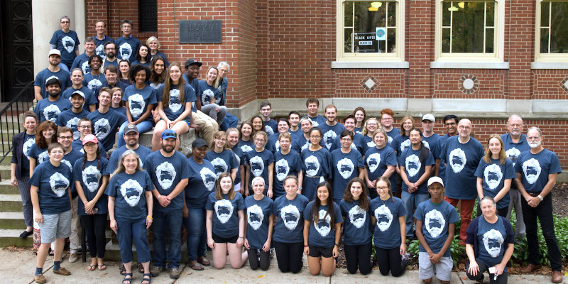 Faculty, staff and students on steps of alumni hall, all wearing tom dutton legacy t-shirts