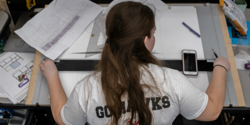 Viewed from behind, a female student is looking at her drawings on her desk