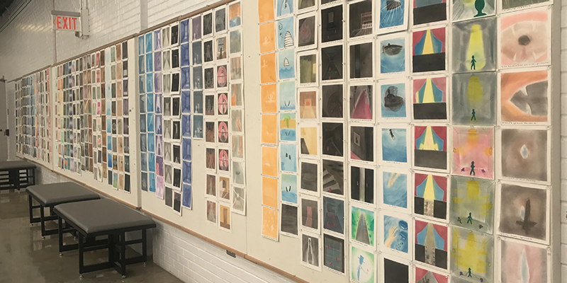 An assortment of student graphic work covers the atrium wall like a quilt