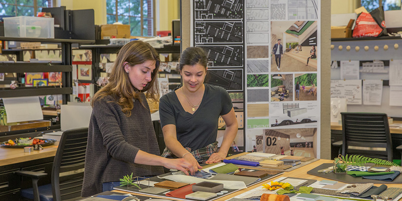 Two female students touch a project on a tabletop in studio during open house