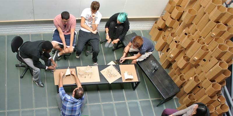 A birdseye view of students and faculty discussing sketches and models in the atrium