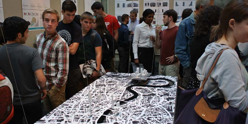 Visitors mill around a tabletop rendering of a map of London