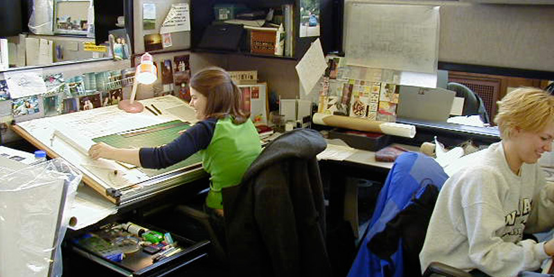 Two smiling women work across from each other in a drawing studio