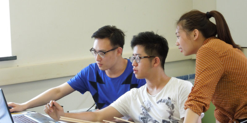 3 students gather in front of a computer as they work on a project