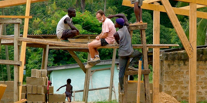 Professor and local workers on a crossbeam of a construction project