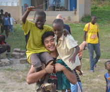 A student poses with two village children on his shoulders