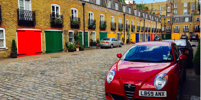 London Mews. A cobblestone street is lined with colorful buildings. Cars are parked along the street