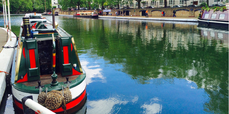 London Regents Canal. A red and white boat is in the foreground.