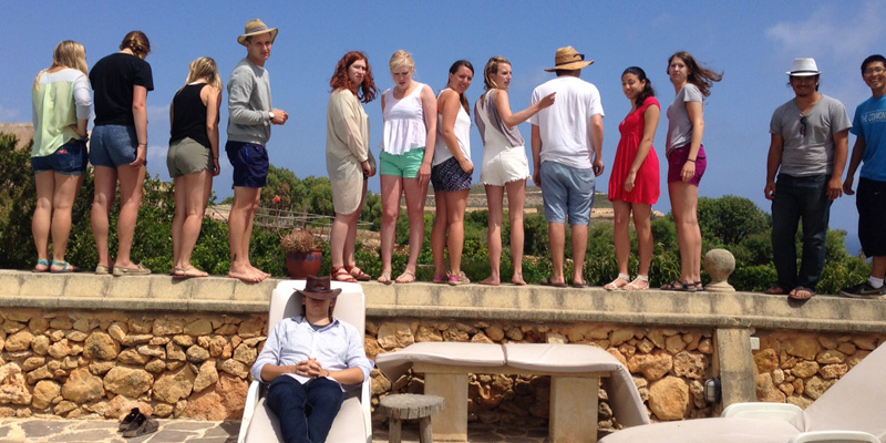 Students stand on a stone wall as a man wearing a cowboy hat over his eyes reclines in a lounger in Malta