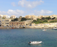 A view from a body of water looking toward distant buildings along the shore of Malta