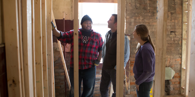Students are seen behind framing in an Over-the-Rhine building