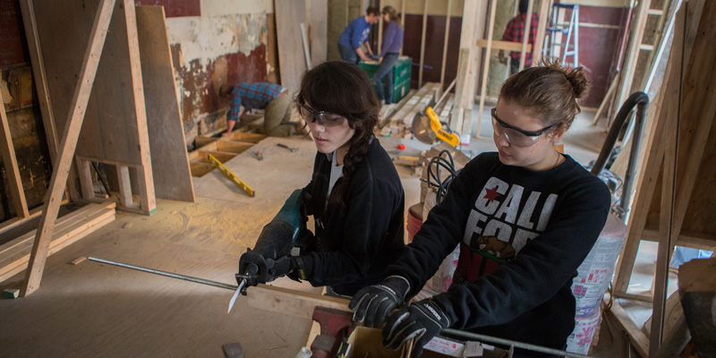 2 female students work construction at Over-the-Rhine rehab site