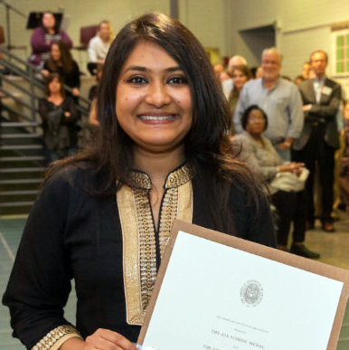 A smiling student holds a framed award certificate