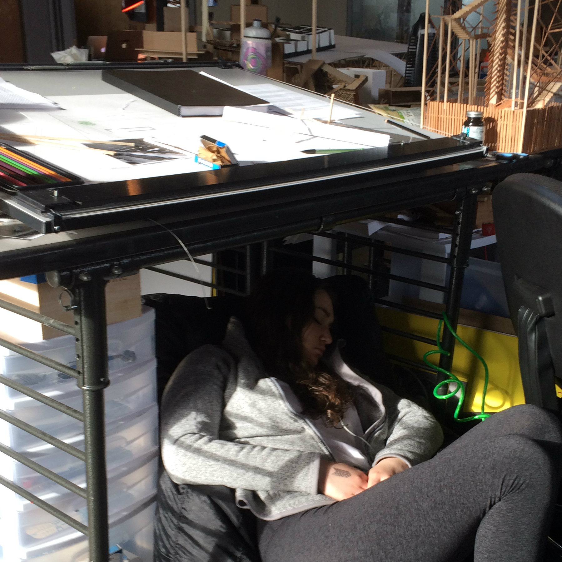 student sleeping on a bean bag under a desk