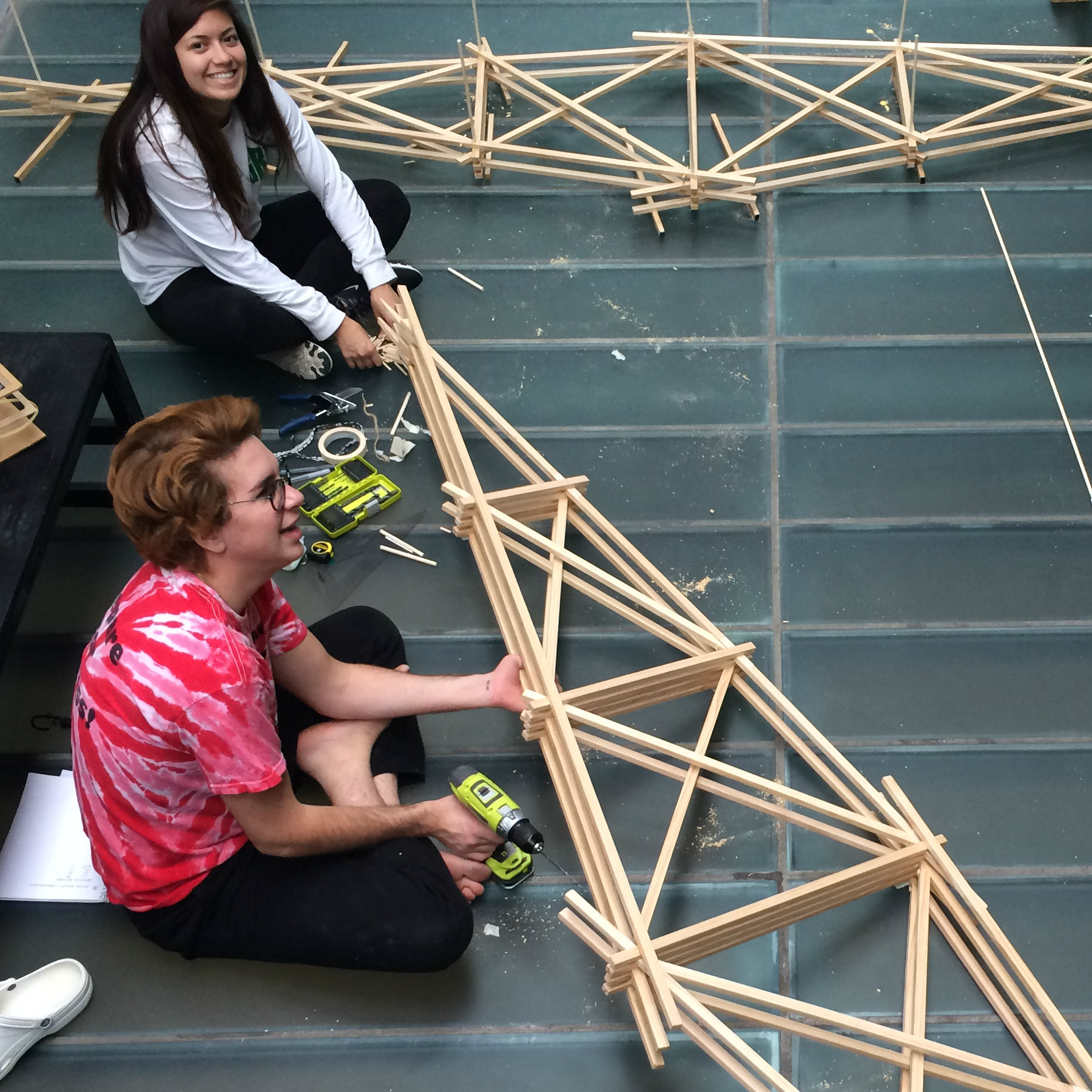 students sitting on floor of atrium with large bridge models